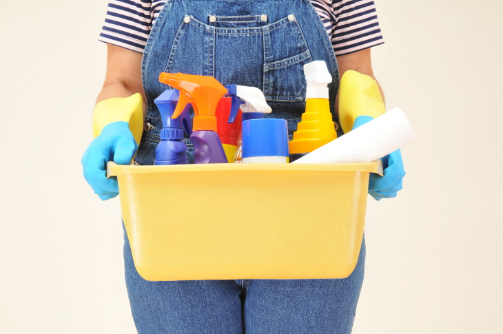 cleaning chemicals you should never mix woman holding cleaning supplies