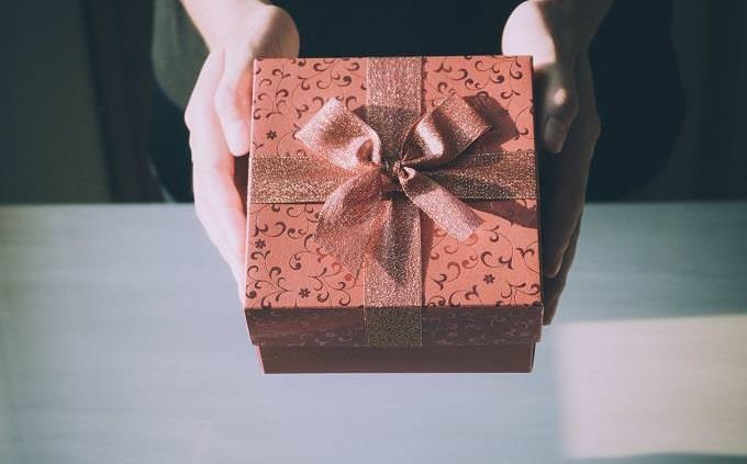 Unas manos entregando un regalo
