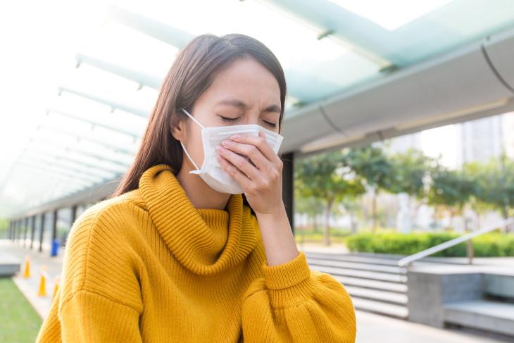 allergies vs coronavirus woman in mask sneezing