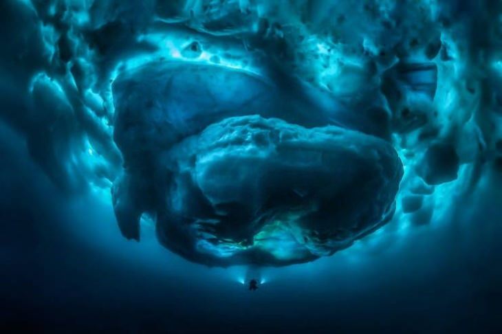 human scale photos A Diver Compared to the Underwater Mass of an Iceberg