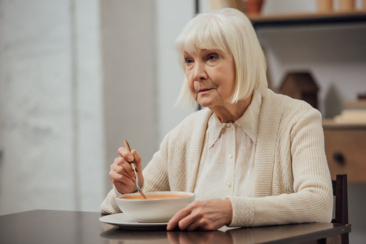 Foods That Increase the Risk of Alzheimer's and Dementia sad woman eating soup
