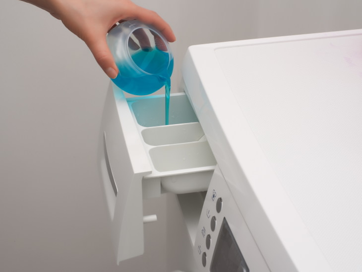 Face Mask Cleaning Mistakes pouring detergent into a washing machine