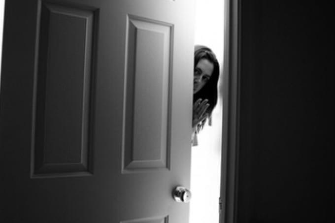 woman slowly opening door