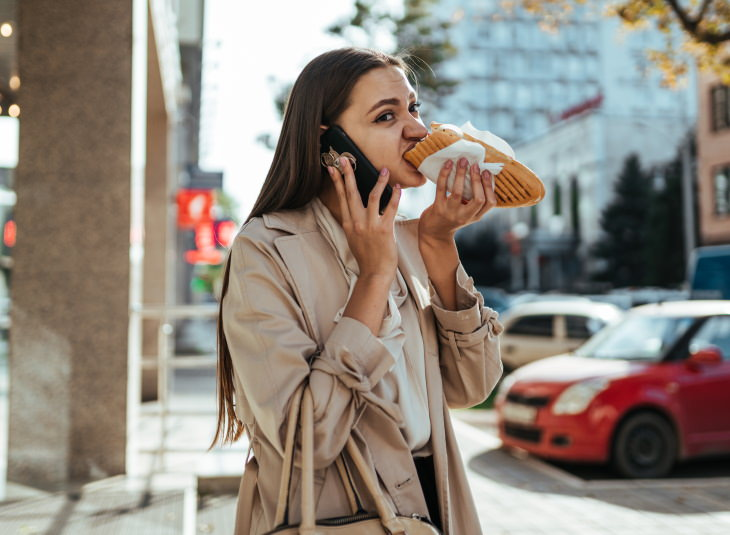 How to Eat Healthy When You're Stressed woman eating toast on her way to work