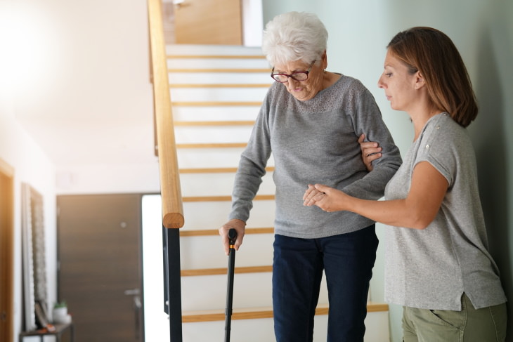 Hearing Loss Commorbidities Woman helping elderly lady go down the stairs