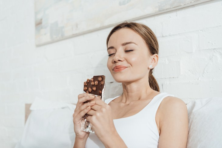 Nourishing vs Toxic Pleasure: What is the Difference? woman enjoying chocolate bar