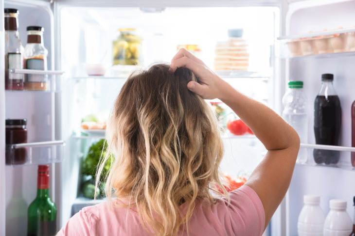 How to Go Grocery Shopping Less Often woman in front of the fridge