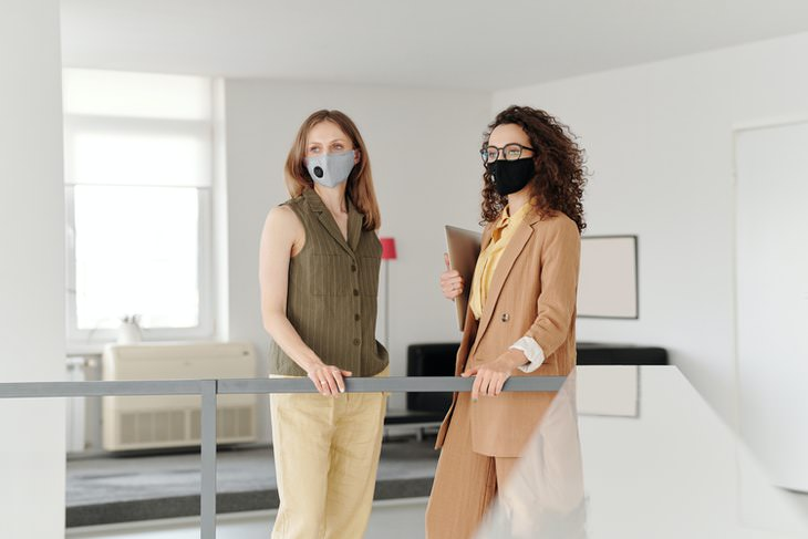 Face Masks Reduce the Severity of the Disease two women in office wearing face masks