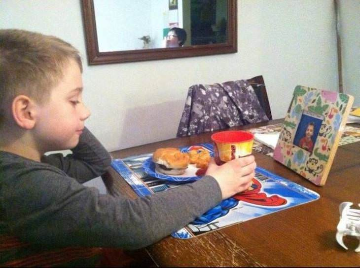 18 Photos of Kids in Hilariously Weird Situations, eating in front of his own pictures