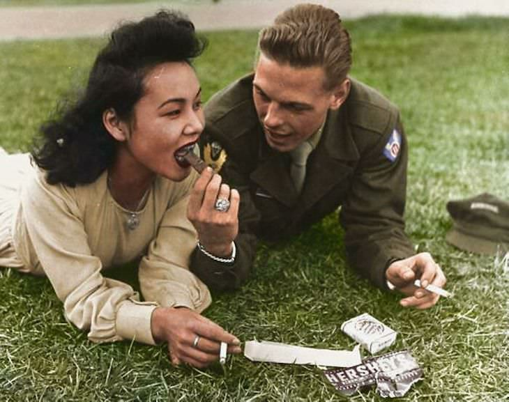 Rare and Beautifully Colorized Historical Photo US soldier from the 11th Airborne Division shares a bit of chocolate with a local girl, 1946, Japan