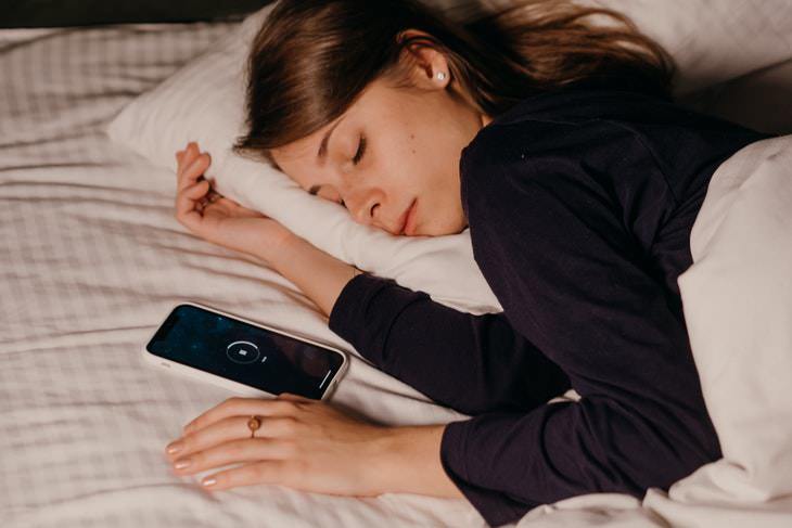 how to get back to sleep when you wake up at night woman sleeping next to a phone
