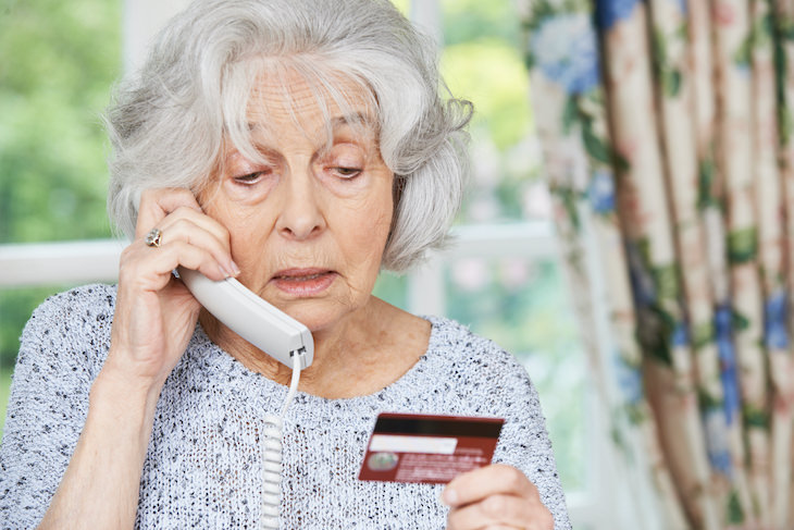 Covid-19 Vaccination SCAMS To Watch Out For senior woman paying over the phone