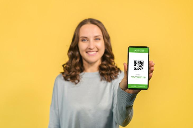 COVID-19 Vaccine Passports woman holding digital pass