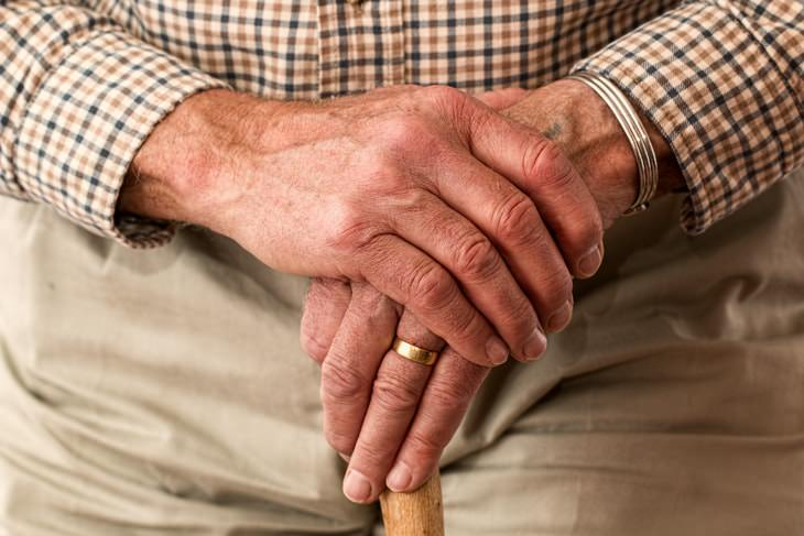 Stages of Parkinson's Disease hands of older man with cane