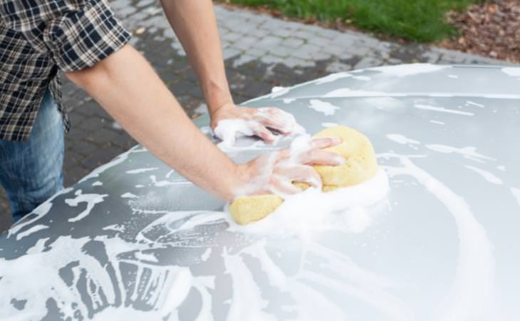 man cleaning car hood with a sponge