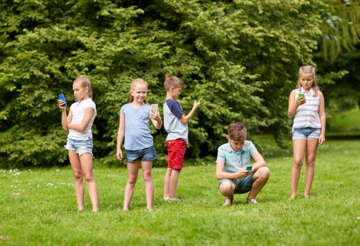 Kids using smartphones on the lawn